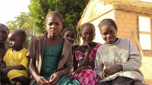 My host sister Khady Fall, far right, with neighborhood kids outside my hut.